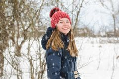 Young beautiful fair-haired girl stands and laughs in the park under soft fluffy snow on a cold winter day.  royalty free stock image