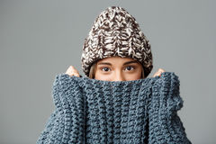 Young beautiful fair-haired girl wearing knited hat and sweater hiding her face in collar looking at camera over grey Stock Images