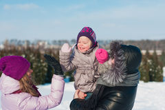Young beautiful family in bright clothes winter fun jumping and running, snow, lifestyle, winter holidays Royalty Free Stock Photography