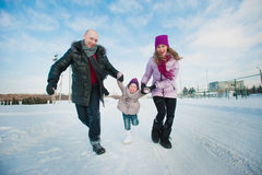 Young beautiful family in bright clothes winter fun jumping and running, snow, lifestyle, winter holidays stock photo