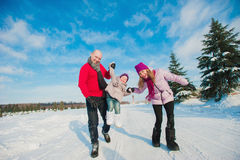 Young beautiful family in bright clothes winter fun jumping and running, snow, lifestyle, winter holidays Royalty Free Stock Photos