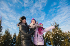 Young beautiful family in bright clothes winter fun jumping and running, snow, lifestyle, winter holidays Royalty Free Stock Photo