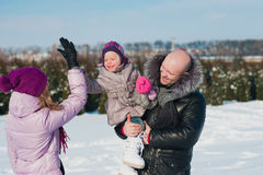 Young beautiful family in bright clothes winter fun jumping and running, snow, lifestyle, winter holidays Stock Image