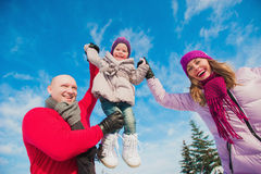 Young beautiful family in bright clothes winter fun jumping and running, snow, lifestyle, winter holidays Stock Photography