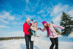 Young beautiful family in bright clothes winter fun sledding, snow, lifestyle, winter holidays Royalty Free Stock Images