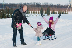Young beautiful family in bright clothes winter fun sledding, snow, lifestyle, winter holidays Stock Photography