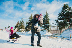 Young beautiful family in bright clothes winter fun sledding, snow, lifestyle, winter holidays Stock Photo