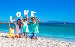 Young beautiful family of four  with word love on Stock Photos
