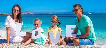 Young beautiful family of four  with word love on Stock Photography