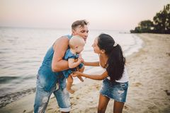 A young, beautiful family of three. Mom, Dad and daughter in the arms of my father play, rejoice, smile on the sandy beach on the. Beach in the summer. Dressed royalty free stock photo