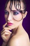 Young beautiful fashion model with pink and blue makeup and hairstyle on her face. Stock Images