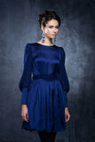 Young and beautiful fashion model posing in a blue dress Stock Photos
