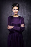 Young and beautiful fashion model posing in a purple dress Stock Images