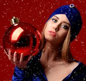 Young beautiful fashion woman in blue stylish winter dress and hat hold big christmas decoration ball Royalty Free Stock Images