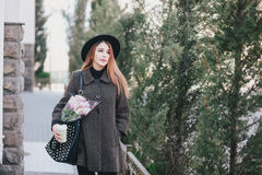 Young beautiful fashion woman wearing hat posing with flowers in her bag and coffee Stock Photography
