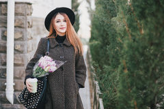 Young beautiful fashion woman wearing hat posing with flowers in her bag and coffee Stock Images