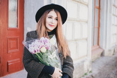Young beautiful fashion woman wearing hat walking on a city streets with flowers Royalty Free Stock Image