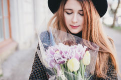 Young beautiful fashion woman wearing hat walking on a city streets with flowers Stock Photos