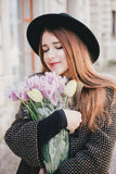 Young beautiful fashion woman wearing hat walking on a city streets with flowers Stock Images