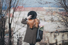 Young beautiful fashion woman wearing hat walking on a city streets with flowers Royalty Free Stock Photos