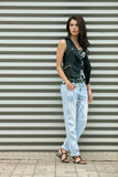 Young beautiful fashionable brunette woman in black leather jacket posing outdoors against urban style background of metal strips Royalty Free Stock Image