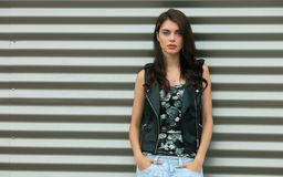 Young beautiful fashionable brunette woman in black leather jacket posing outdoors against urban style background of metal strips Stock Photo