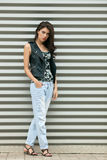 Young beautiful fashionable brunette woman in black leather jacket posing outdoors against urban style background of metal strips Royalty Free Stock Photo