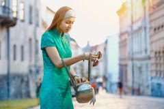 Portrait of a young beautiful fashionable lady. Young beautiful fashionable lady wearing green dress searching for something in her hand bag on a street of the royalty free stock photo