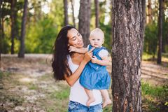 Young beautiful fashionable mother with long brunette hair holding a daughter`s blonde with blue eyes one year of birth in a royalty free stock image