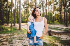 Young beautiful fashionable mother with long brunette hair holding a daughter`s blonde with blue eyes one year of birth in a royalty free stock images
