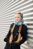 Young beautiful fashionable redhead woman with braids hairdo in blue white headcraft stylish denim black trench jacket posing outd Royalty Free Stock Images