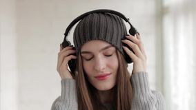 Young beautiful fashionable woman in big dj headphones phones enjoying music indoors stock video