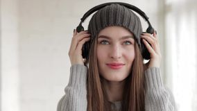Young beautiful fashionable woman in big dj headphones phones enjoying music indoors stock video footage