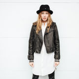 Young beautiful fashionable woman in leather jacket and  black hat posing outdoors Stock Image