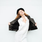 Young beautiful fashionable woman in leather jacket and white blouse posing against garage door Stock Photo