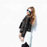 Young beautiful fashionable woman in leather jacket and white blouse posing against garage door Stock Images