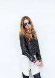 Young beautiful fashionable woman in leather jacket and white blouse posing outdoors against garage door Royalty Free Stock Photos