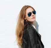 Young beautiful fashionable woman in leather jacket and white blouse posing outdoors against garage door Stock Photos