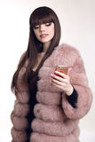 Young beautiful fashionable woman in pink fur coat holding mobil. E phone  on white background. Trendy hairstyle. Brown haired Royalty Free Stock Photography