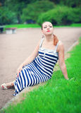 Young beautiful fashionable woman sitting on the lawn Royalty Free Stock Images