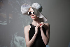Young beautiful fashionable woman with trendy makeup. Model looking at camera, wearing stylish eyeglasses, hat. Female fashion, be Royalty Free Stock Images