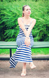 Young beautiful fashionable woman wearing striped dress sitting. On the bench outdoor Stock Photography