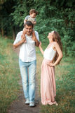 Young beautiful father, mother and little toddler son against green trees Stock Image