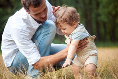 Young beautiful father, mother and little toddler son against green trees Stock Photo