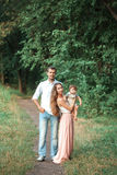 Young beautiful father, mother and little toddler son against green trees royalty free stock photos