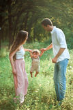Young beautiful father, mother and little toddler son against green trees stock photos