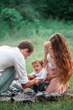 Young beautiful father, mother and little toddler son against green trees royalty free stock image
