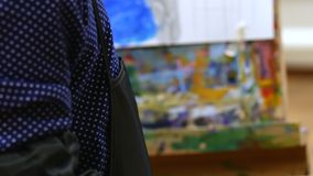 Young cute Female Artist is in an Art Studio, Sitting Behind an Easel and Painting on Canvas. Drawing Process: in the. Young Beautiful Female Artist is in an Art stock footage