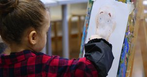 Young cute Female Artist is in an Art Studio, Sitting Behind an Easel and Painting on Canvas. Drawing Process: in the. Young Beautiful Female Artist is in an Art stock video footage