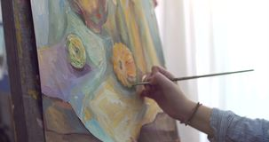 A Young Beautiful Female Artist is in an Art Studio, Sitting Behind an Easel and Painting on Canvas. Drawing Process: in